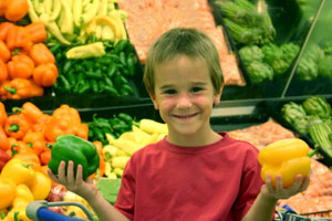 Boy in green grocers holding peppers